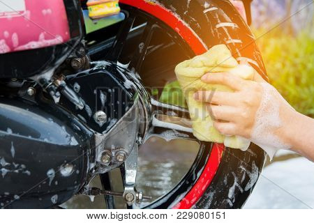 Motorcycle Clean,female Hand With Yellow Foam Sponge Washing A Motorcycle.