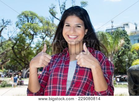 Caucasian Woman With Hipster Shirt Showing Both Thumbs Outdoors In Summer In City