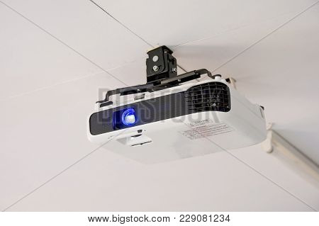 White Projector Hanging On The Ceiling Of Conference Room.