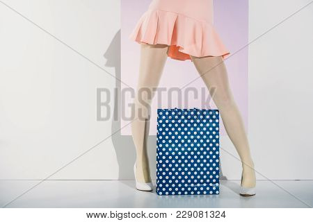 Low Section Of Stylish Girl In Pink Skirt Standing With Shopping Bag On Grey