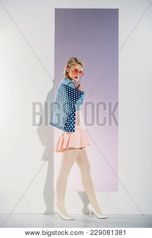 Beautiful Stylish Young Woman Holding Shopping Bag And Looking At Camera In Studio
