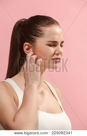 Sore Ear. Ear Ache Concept. The Sad Crying Woman With Headache Or Pain On Trendy Pink Studio Backgro