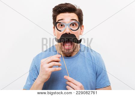 Shocked man in fake mustache and eyeglasses looking at the camera with open mouth over grey background