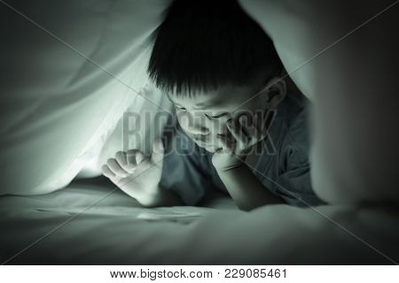 Little Boy Watching Online Tablet While Lying On Bed Under White Duvet, In The Bedroom At Night, Bri