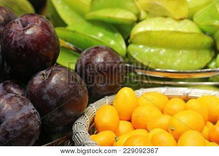 Exotic Fruits In Baskets: Cumquats, Star Fruits And Plums