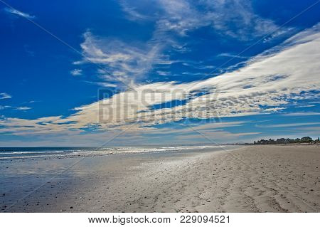 Wide Sandy Beach At Low Tide With Cloudy Blue Sky