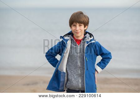 Young boy posing at the winter beach. Cute smiling happy 11 years old boy at seaside, looking at camera.