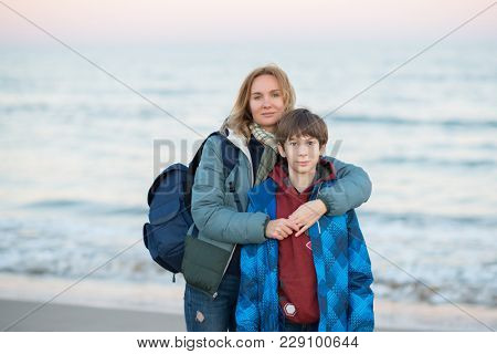 Young boy with his mother posing at the winter beach over sea view. Cute 11 years old boy at seaside with  his mom, evening time. Family outdoor portrait.