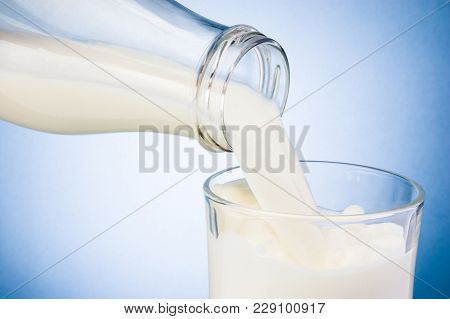 Pouring Milk From Bottle Into Glass On Blue Background