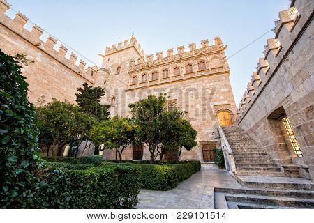Ancient stock exchange, Valencia, Spain. Antique building. Silk exchange, outdoor, general view with orange garden.