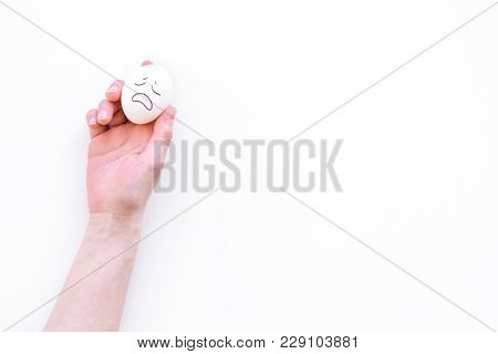 Emotion Management Concept. Suppression Anger. Angry Face Drawn On Egg. White Background Top View.
