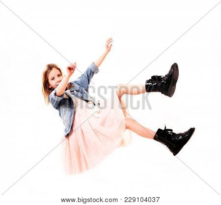Lovely little girl is falling down with legs up. Isolated on white background. Studio shot.