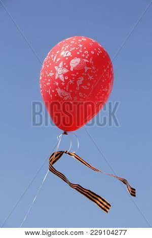 Air Balloon With A St. George Ribbon Tied To It Against The Background Of A Cloudless Blue Sky.