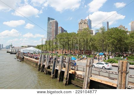 New York, Usa - July 6, 2013: People Walk In Battery Park In New York. Almost 19 Million People Live