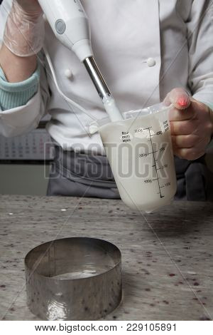 The Master Pastry Chef Mixing Icing For A Cake Blender In Order To Release The Air From The Glaze An