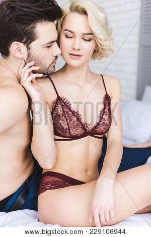 Sexy Young Woman In Lingerie Touching Handsome Boyfriend On Bed