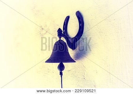 The Hanging Bell. An Old Rusty Bell On A Stone Wall. The Bell Is Used To Make A Call Inside The Hous