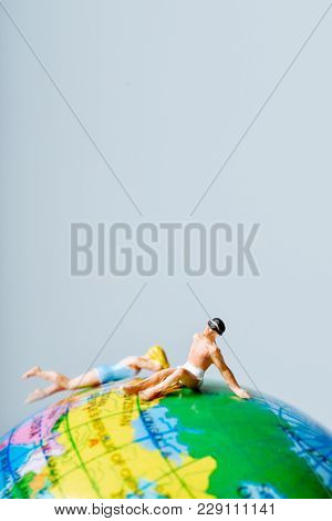 a miniature woman and a miniature man wearing swimsuit on the top of a terrestrial globe, and some blank space on top