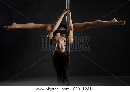 Slim Brunette In Top And Shorts Exercising On Pylon Hanging On It View In Dark Room