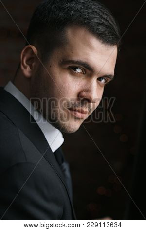 Portrait Of A Man In A Black Jacket Turned Into Darkness. Business Portrait In A Low Key Of A Stylis