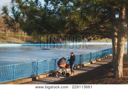 Young Woman In Blue Coat Walking In Winter Park Near Frozen Lake With Little Child Baby In Orange Ba