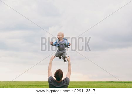 Joyful Man Walk On Green Field, Rest, Have Fun, Play, High Toss Up Little Cute Child Baby Boy On Sky