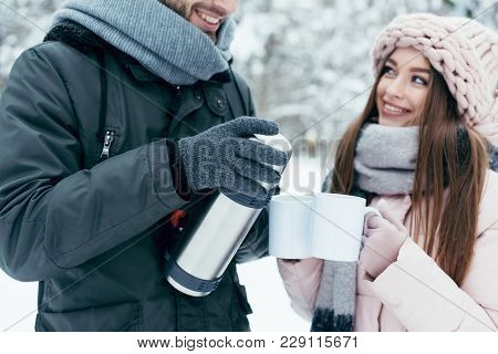 Partial View Of Couple Drinking Tea From Thermos In Winter Park