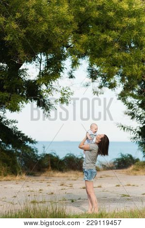 Young Fun Smiling Woman Standing At Sea Background Hugging Little Cute Child Baby Boy On Nature, Gre
