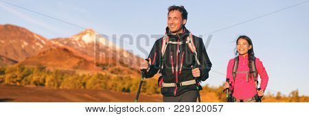 Hiking hikers couple trekking in nature mountains at sunset with walking poles and backpack wearing outdoor gear jackets. Happy multiracial group of friends, man and woman hiking banner panorama.