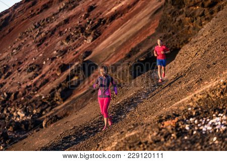 Sport athletes on trail run exercising cardio training together in summer outdoors at sunset. Afternoon couple workout running in mountain landscape, volcano cliff. People healthy and active.