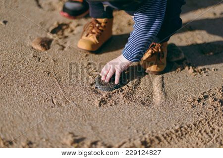 Close Up Of Legs Kid Boy In Yellow Boots On Sand Of Sea Sunny Beach. Child Little Feet Walking On Na