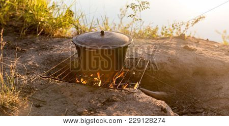 Cauldron On Fire At Sunset . In The Park In Nature