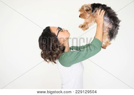 Closeup Portrait Of Smiling Young Attractive Woman Raising Yorkshire Terrier And Sending Him Air Kis