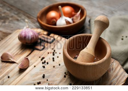 Wooden kitchen utensils with ingredients on table