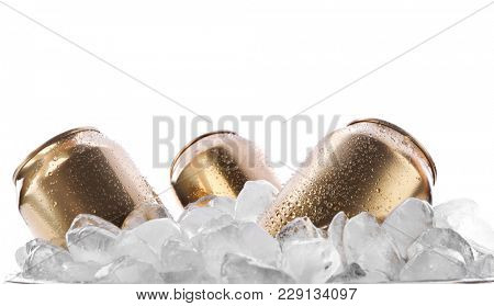 Cans of beer in ice on white background