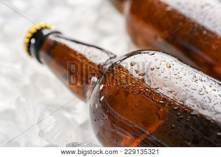 Bottles of fresh beer on ice, closeup
