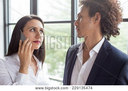Serious Business Woman Looking At Coworker When Calling On Phone. Anxious Business Lady Talking On P