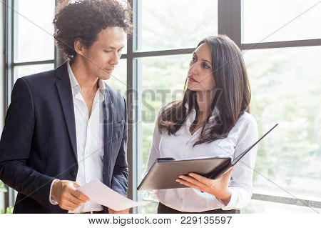 Unsmiling Woman Showing Annual Report To Entrepreneur. Female Executive Sharing Her Business Idea Wi