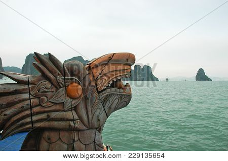 A Close-up Shot Of A Dragon Figurehead On The Prow Of A Boat. Rocks And Islands Of Halong Bay Are In