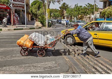 Kashan, Iran - April 27, 2017: Aged Man Pushed Hand Trolley Up Front Of Him On Carriageway Of City S