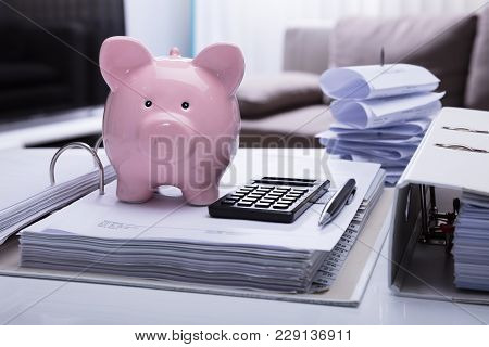 Close-up Of Piggybank And Document With Receipts And Calculator On White Desk
