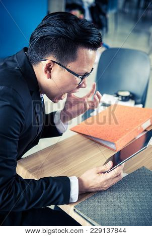 Asian Businessman Working On Tablet, Pressured To Work And Unsuccessful