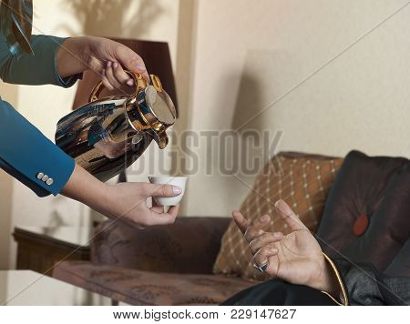 Waitress Serving Arabic Coffee To A Wealthy Arab Man