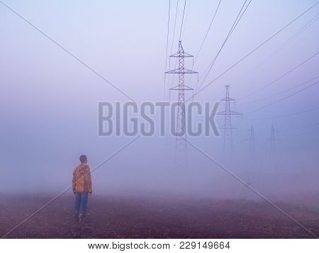 Transmission Towers And Man In The Fog At The Background Of The Dawn Sky. High Voltage Power Line Si