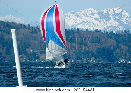 Single Boat Coming Into Leeward Marke Under Spinnaker With Olympic Mountains In Background.