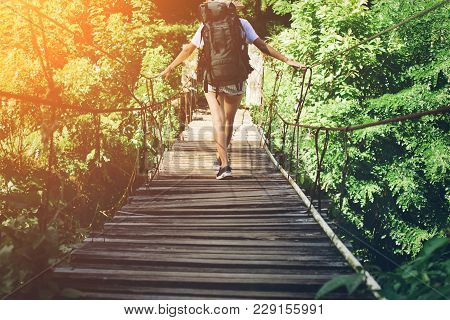 Young Woman With Backpack Traveling Over Hanging Bridge In Green Forest, Intentional Sun Glare