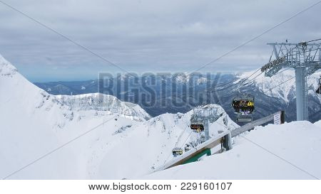 Open Four-seater Chair Lifts In The Mountains Bring Skiers And Snowboarders To The Place Where The D