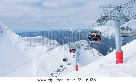 Four-seater Chair Lifts In The Mountains Bring Skiers And Snowboarders To The Place Where The Descen