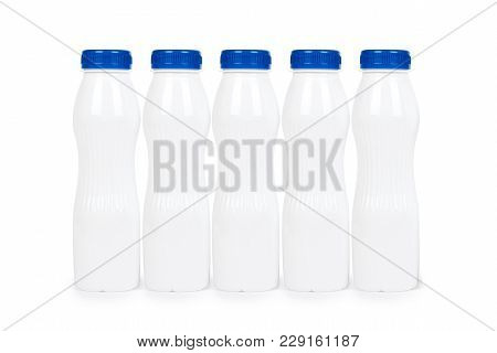 Row Of White Plastic Bottles With Drink Yogurt Or Milk. Isolated On White Background. Container Merc
