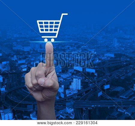 Hand Pressing Shop Cart Icon Over Modern City Tower, Street And Expressway, Shopping Online Concept